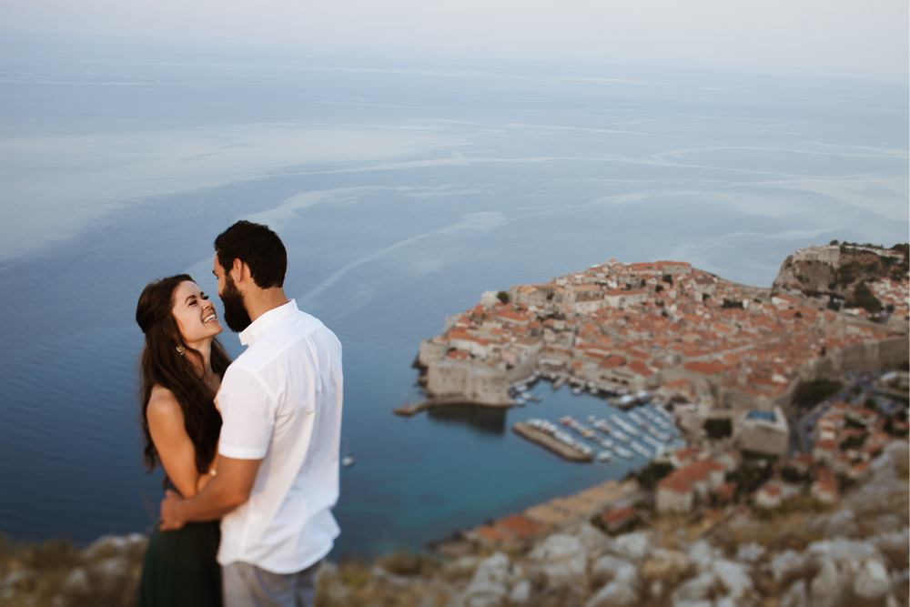 Picture of a newlywed couple during the after wedding photo session in Dubrovnik, with the Old City of Dubrovnik in the background.