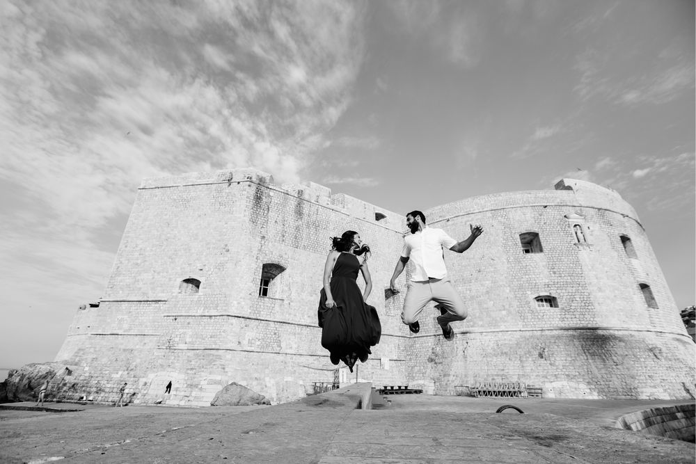 Joyful couple jumping in front of St. John Fort in Dubrovnik.