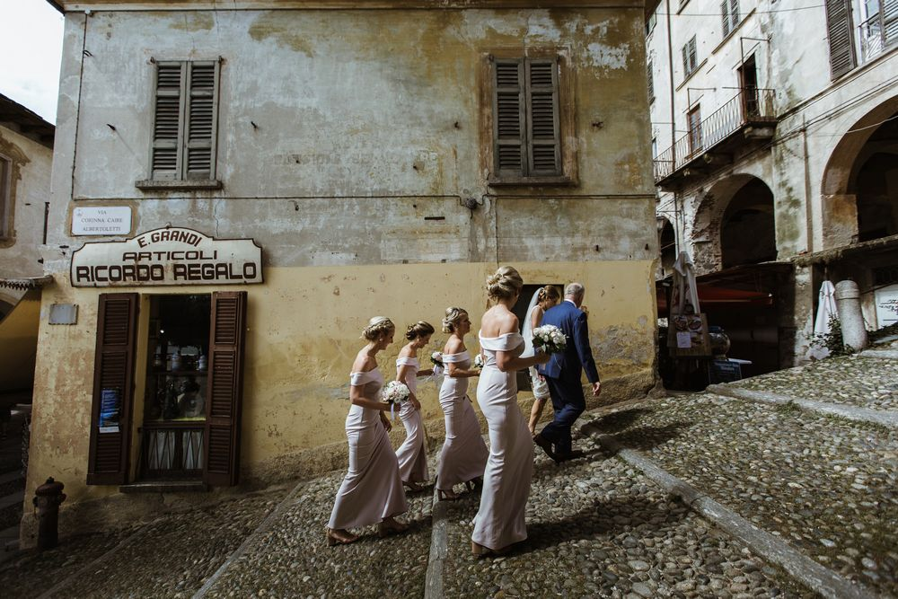 A wedding bridal party walking up to the Santa Maria Assunta Church in Lake Orta a moment before the wedding ceremony . Image by DT studio - Lake Orta Wedding photographer & Videographer